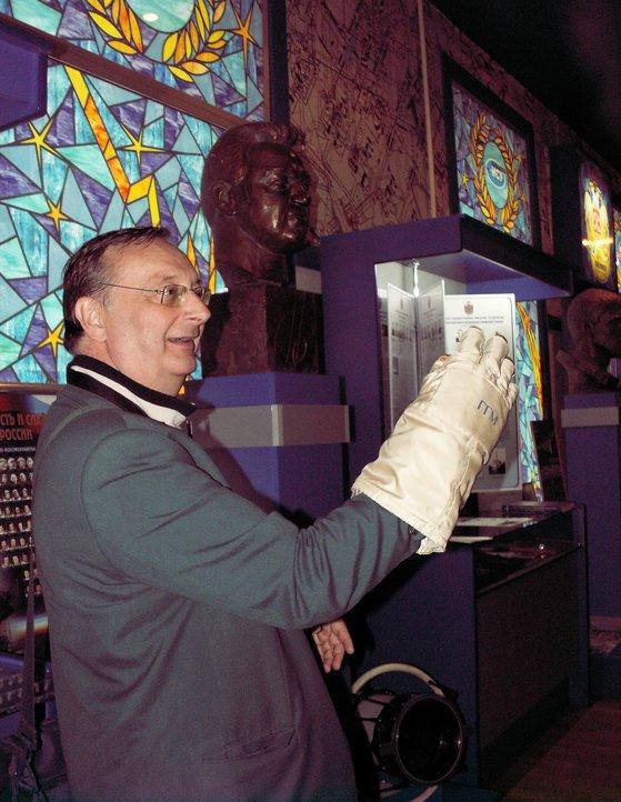 Кристиан Лардье в Музее БГТУ (Военмеха) примеряет перчатку космического скафандра Г.М. Гречко. Фото В.В. Лебедева.